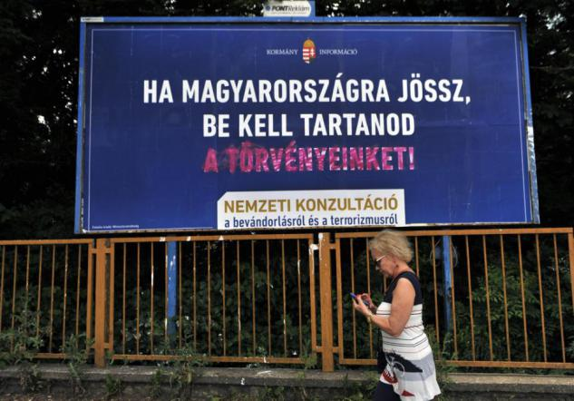 """FOR STORY: HUNGARY BILLBOARD BATTLE - A woman is walking in front of a vandalized anti immigration billboard reading """"If you come to Hungary, you have to respect our laws!"""" in Budapest, Hungary, on June 15, 2015. Hungary's central-right government has launched a controversial billboard campaign against immigration while UNHCR introduced its counter campaign highlighting successful refugee stories.  (AP Photo/Bela Szandelszky)"""